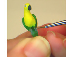 Painting the feet of the polymer clay miniature dollhouse parrot